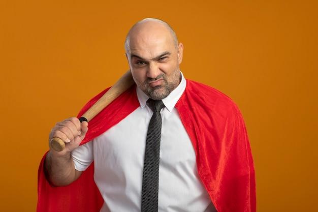 Zły biznesmen super bohater w czerwonej pelerynie, trzymając kij baseballowy na ramieniu, patrząc z przodu z poważnym wyrazem pewności, stojąc na pomarańczowej ścianie