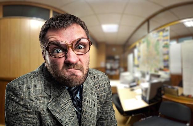 Zły biznesmen w okularach patrzący na ciebie