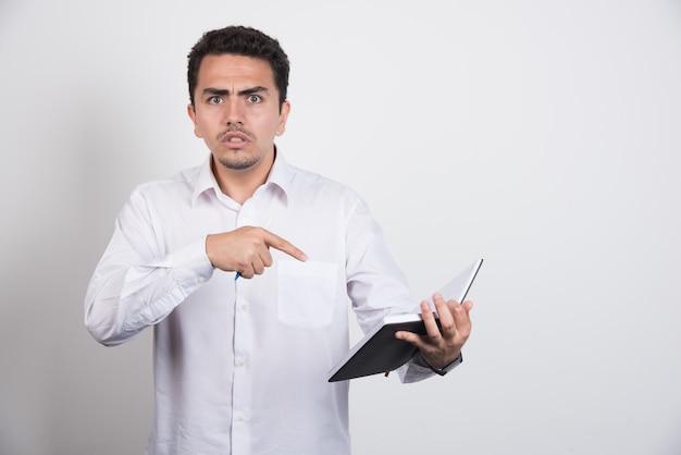 Zły biznesmen, wskazując na notebook na białym tle.