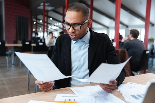 Zły biznesmen z dokumentami i laptopem w biurze