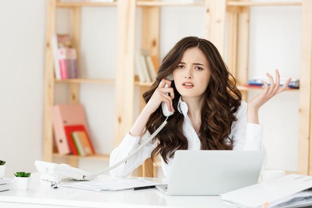 Zły bizneswoman krzyczy na telefon w nowoczesnym biurze