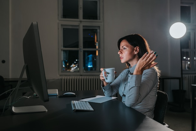Zły bizneswoman patrzeje ekran komputerowego przy nocą. widok z boku.
