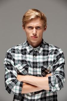 Zły blond przystojny młody mężczyzna ubrany w swobodną kraciastą koszulę z rękami skrzyżowanymi na piersi w kolorze szarym