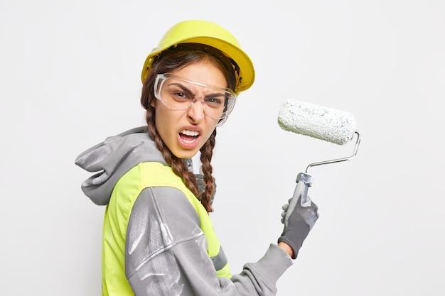 Zły brygadzista lub robotnik uśmiecha się twarz trzyma wałek nosi ochronne twarde okulary przezroczyste okulary zaangażowane w majsterkowanie i renowację na białym tle na białej ścianie. zirytowany pracownik budowlany