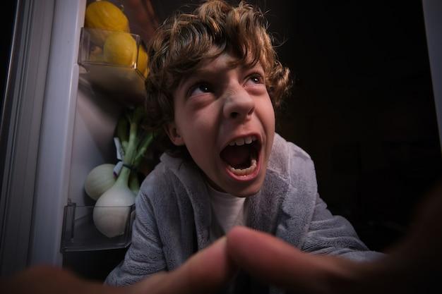Zły chłopiec w pobliżu lodówki z produktami w ciemnej kuchni