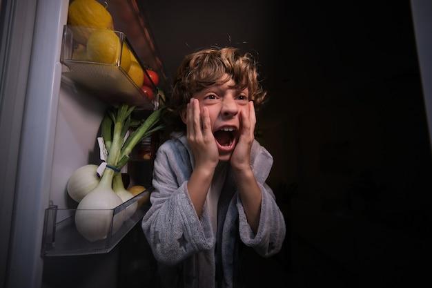 Zły chłopiec w pobliżu otwartej lodówki w nocy?