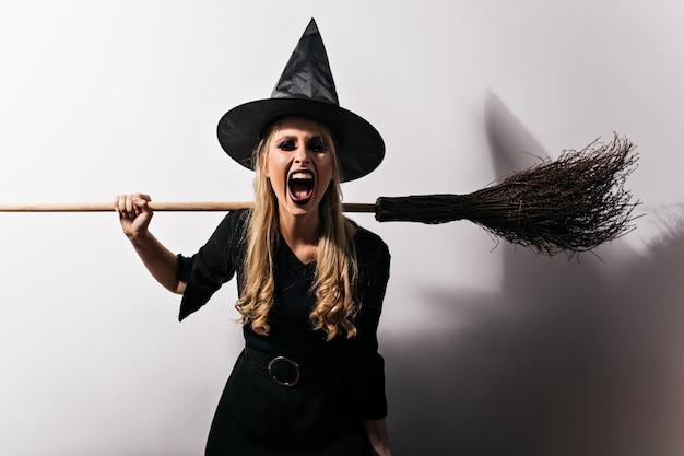 Zły czarownica z długimi włosami trzyma miotłę. blondynka czarodziejka krzyczy w halloween.