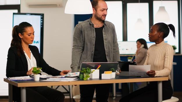 Zły człowiek biznesu krzyczy na różnych kolegów podczas spotkania w biurze, wyrzucając dokumenty, nie zgadzając się na złą umowę biznesową. młoda wielorasowa grupa ludzi pracujących w przestrzeni coworkingowej.