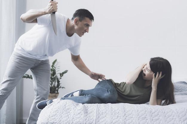 Zły człowiek grozi przerażonej żonie z nożem w domu