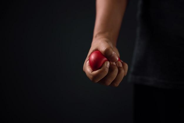 Zły człowiek. ręka z czerwonym plastikowym sercem. gotowy do uderzenia. przycięte i selektywne ustawianie ostrości