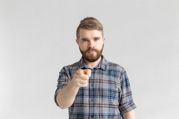 Zły człowiek z brodą, palcem wskazującym w kierunku aparatu na białym tle