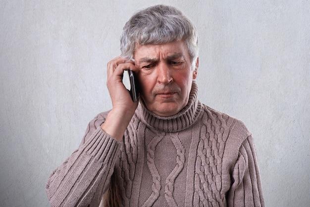 Zły dojrzały mężczyzna o siwych włosach i zmarszczkach, trzymający w ręku smartfon komunikujący się z dziećmi