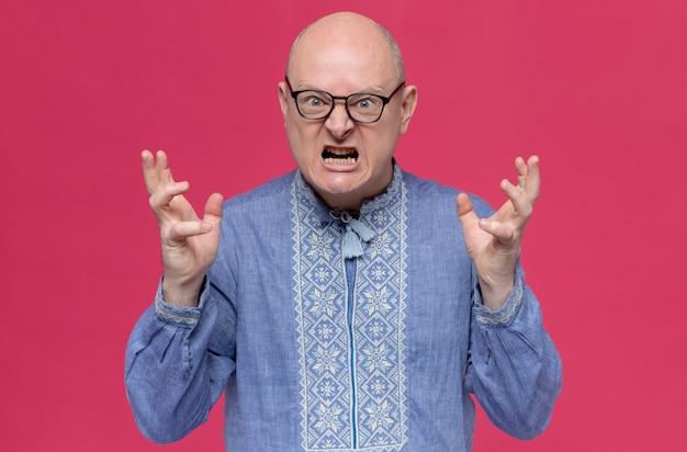 Zły dorosły słowiański mężczyzna w niebieskiej koszuli w okularach optycznych trzymających otwarte ręce i