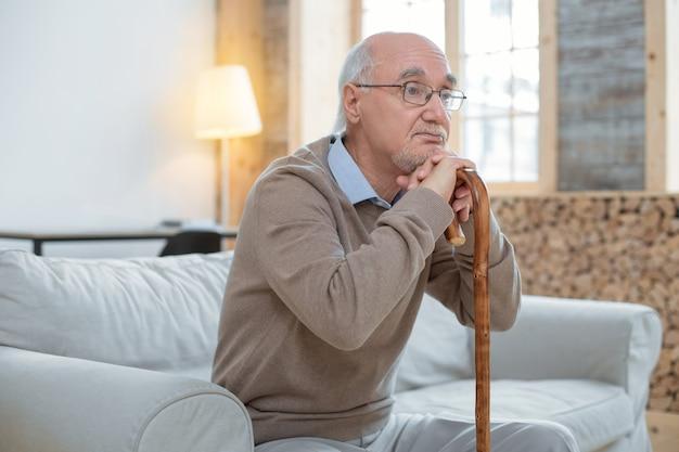Zły dzień. atrakcyjny, przemyślany, starszy mężczyzna, opierając się na lasce, mając na sobie okulary i siedząc na kanapie
