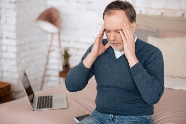 Zły dzień. portret starszego przystojnego mężczyzny siedzącego na łóżku i dotykającego jego skroni z powodu strasznego bólu głowy.