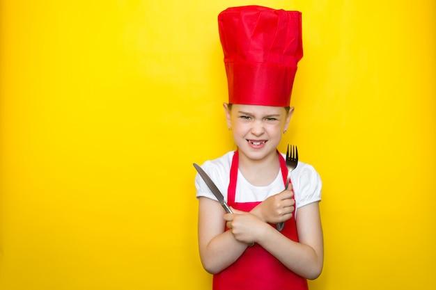 Zły dziewczyna w czerwonym garniturze szefa kuchni, trzymając łyżkę i widelec, ręce skrzyżowane na żółto