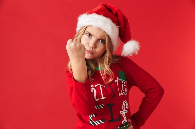 Zły dziewczynka ubrana w świąteczny kapelusz stojący na białym tle, pokazując jej pięść