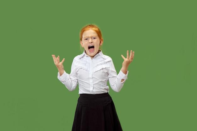 Zły emocjonalna dziewczyna krzyczy na białym tle na zielonej ścianie