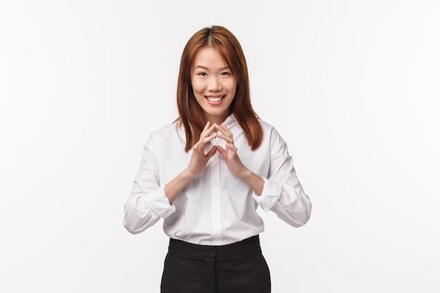 Zły geniusz ma plan. sprytna i kreatywna kombinacja przebiegła azjatycka kobieta przygotowuje świetny pomysł, klepie palce i ohydny uśmieszek, idąc do psikusa współpracownikowi, ma ciekawą myśl na białej ścianie