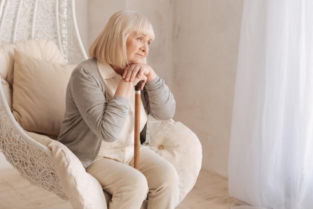 Zły humor. smutna, nieszczęśliwa starsza kobieta siedzi w fotelu i opiera się o laskę, myśląc o swoich problemach