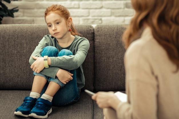 Zły humor. smutna, posępna dziewczyna siedzi na kanapie będąc w złym humorze