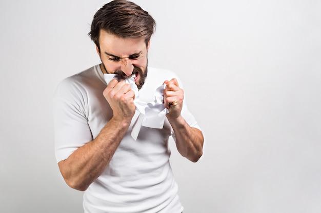 Zły i szalony mężczyzna w białej koszuli rozdziera kiepski papier. pojedynczo na białym