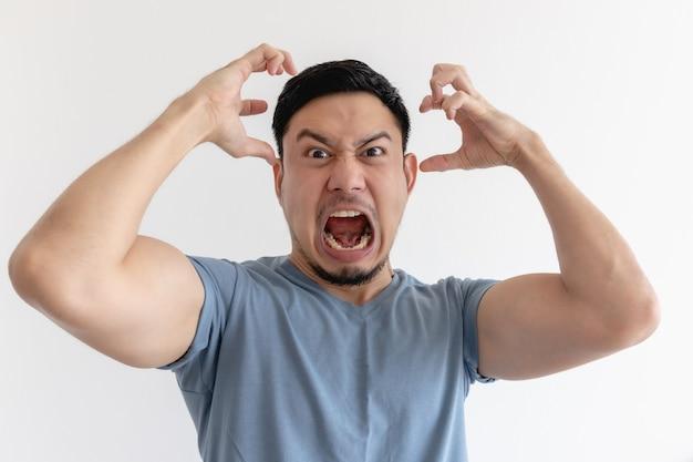 Zły i szalony twarz azjatyckiego mężczyzny w niebieskiej koszulce na na białym tle.