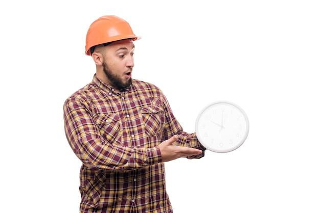 Zły i zszokowany pracownik konstruktora w budowie ochronnej pomarańczowy kask trzyma w ręku duży budzik na białym tle. czas do pracy. czas budowy budynku.
