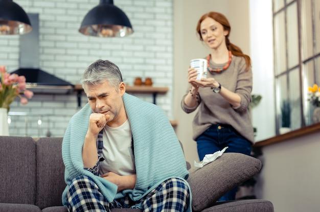 Zły kaszel. smutny, niewesoły mężczyzna siedzi na kanapie i kaszle w pięść