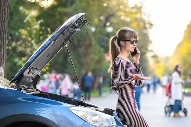 Zły kierowca kobieta rozmawia przez telefon komórkowy z pracownikiem obsługi pomocy stojącej w pobliżu zepsutego samochodu z podniesionym kapturem na poboczu drogi, który ma problemy z jej pojazdem.