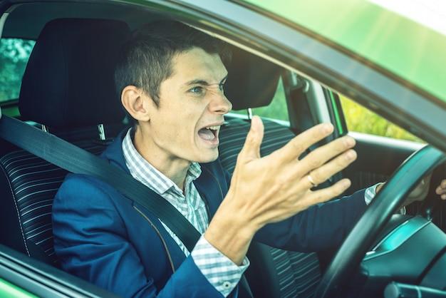Zły kierowca krzyczy w samochodzie