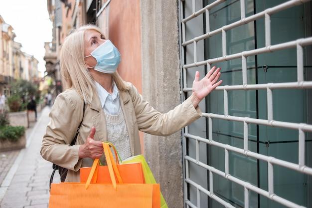 Zły klient przed sklepem zamknięty z powodu pandemii koronawirusa