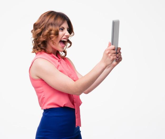 Zły kobieta krzyczy na komputerze typu tablet