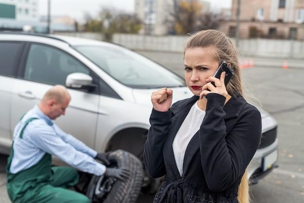 Zły kobieta na usługi samochodowe z zepsutym samochodem