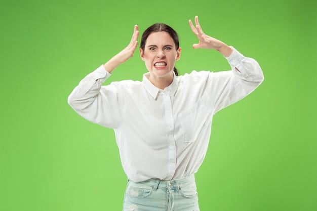 Zły kobieta patrząc na kamery. agresywny biznes kobieta stojąc na białym tle na tle modnego zielonego studia. portret kobiety w połowie długości. ludzkie emocje, koncepcja wyrazu twarzy