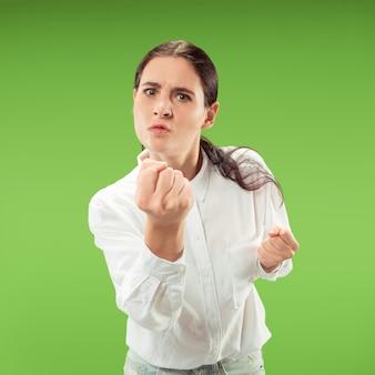 Zły kobieta patrząc na kamery. agresywny biznes kobieta stojąca na białym tle na modnym zielonym tle studio. portret kobiety w połowie długości. ludzkie emocje, koncepcja wyrazu twarzy