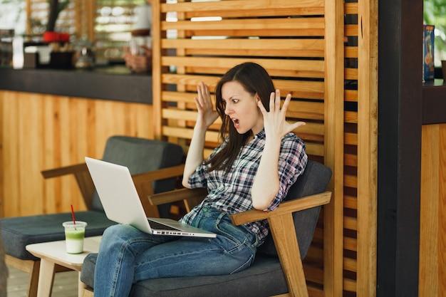 Zły krzyczy smutna zdenerwowana dziewczyna na zewnątrz ulicy kawiarnia drewniana kawiarnia siedzi z nowoczesnym komputerem typu laptop pc, rozkładając ręce w czasie wolnym. biuro mobilne