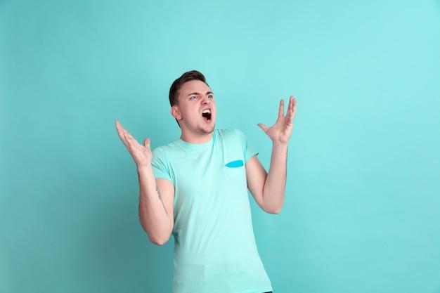 Zły krzyk. kaukaski portret młodego mężczyzny na niebieskiej ścianie studia