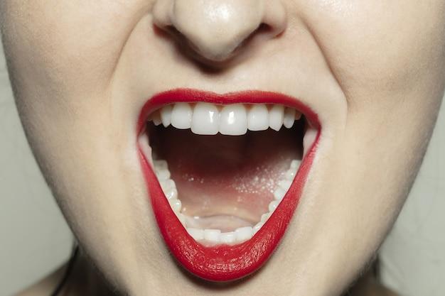 Zły krzyk. zbliżenie na kobiece usta z jasnoczerwonym błyszczącym makijażem ust i dobrze utrzymaną skórą policzków.