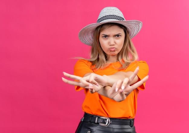 Zły ładna młoda kobieta w pomarańczowej koszulce noszącej okulary przeciwsłoneczne pokazując gest dwóch rąk podczas patrzenia