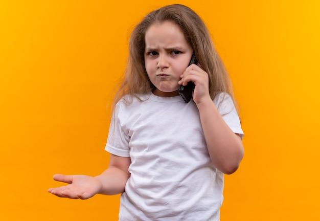 Zły mała uczennica ubrana w białą koszulkę rozmawia przez telefon na odizolowanej pomarańczowej ścianie