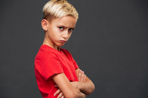 Zły mały chłopiec dziecko z rękami skrzyżowanymi.