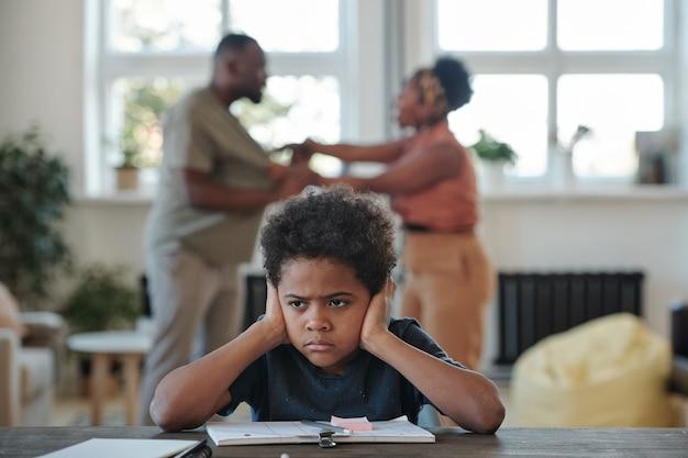 Zły mały chłopiec pochodzenia afrykańskiego zakrywający uszy rękami, próbując wykonać zadanie szkolne przeciwko kłótni rodziców