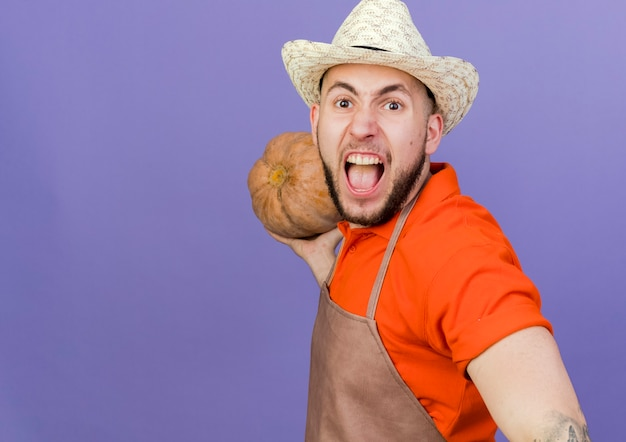 Zły mężczyzna ogrodnik w kapeluszu ogrodnictwo trzyma dyni patrząc