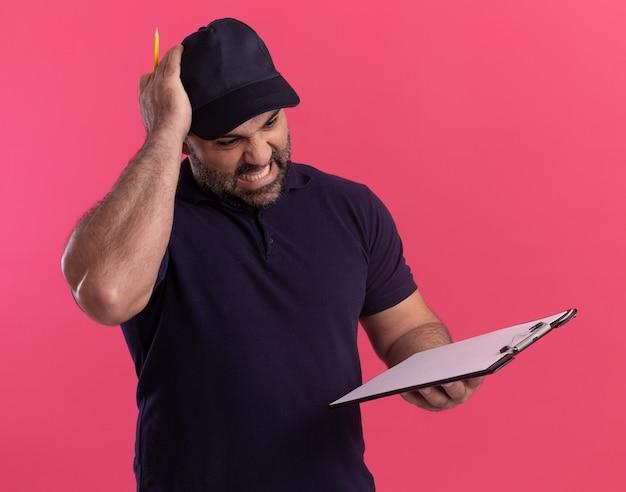 Zły mężczyzna w średnim wieku dostawy w mundurze i czapce, trzymając i patrząc na schowek, kładąc rękę na głowie na białym tle na różowej ścianie