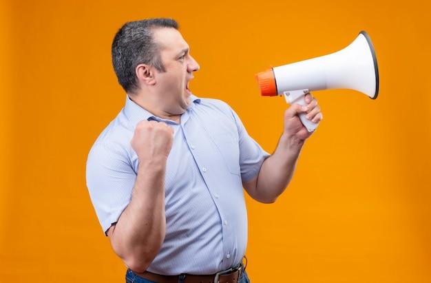 Zły mężczyzna w średnim wieku w niebieskiej koszuli w pionowe paski krzyczy na megafon, stojąc