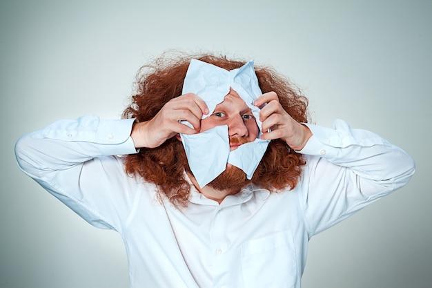 Zły mężczyzna wydziera papier na szaro