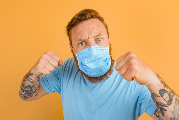 Zły mężczyzna z tatuażem na brodzie i maską na covida chce walczyć