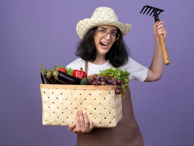 Zły młoda brunetka ogrodniczka kobieta w okularach optycznych iw mundurze na sobie kapelusz ogrodniczy trzyma kosz warzyw i grabie na fioletowej ścianie