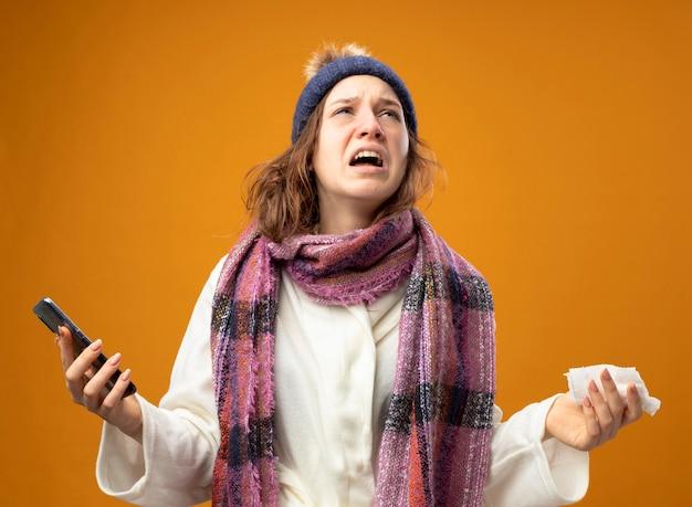 Zły młoda chora dziewczyna ubrana w białą szatę i czapkę zimową z szalikiem, trzymając telefon i serwetkę, rozkładając ręce na białym tle na pomarańczowej ścianie